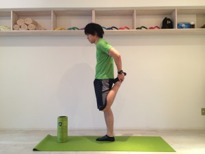膝の痛みを改善する為外側広筋のストレッチを行なう。外側広筋のストレッチは大腿四頭筋の一般的なストレッチを少し変えたものなので、まずは大腿四頭筋の一般的なストレッチを行なう。大腿四頭筋の一般的なストレッチは腰が反らないように行なうべきであり、腰を反らずに出来ている姿勢を横から見た時の画像。