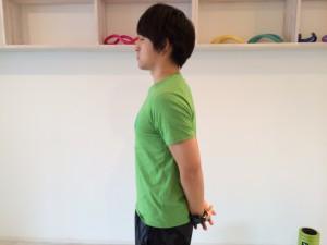 肩こり解消の為の肩甲骨を下げる体操で両手を後ろに組んでいる画像。