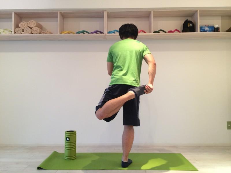 膝の痛みを改善する為外側広筋のストレッチを行なう。外側広筋のストレッチを後ろから見た時、膝が外側に逃げてしまいエラーしている画像