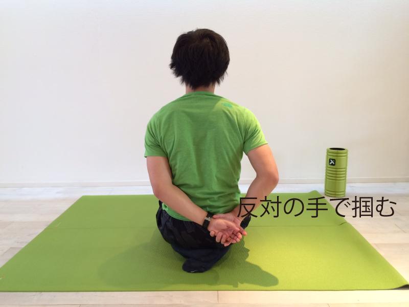 肩こり解消の為の僧帽筋のストレッチのスタートポジション。反対の手で掴む