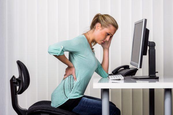 デスクワークの人が日常的に座る時間が長いため腰に痛みが出ている画像。